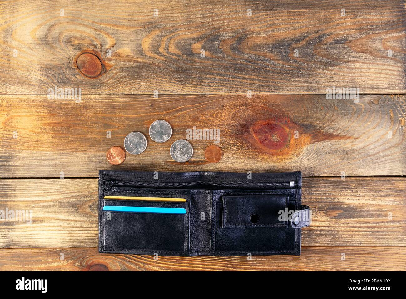 Open black leather pocket wallet with coins one cent and a quarter dollar nearby. Financial crisis, poverty, lack of money. On wooden background or ta Stock Photo