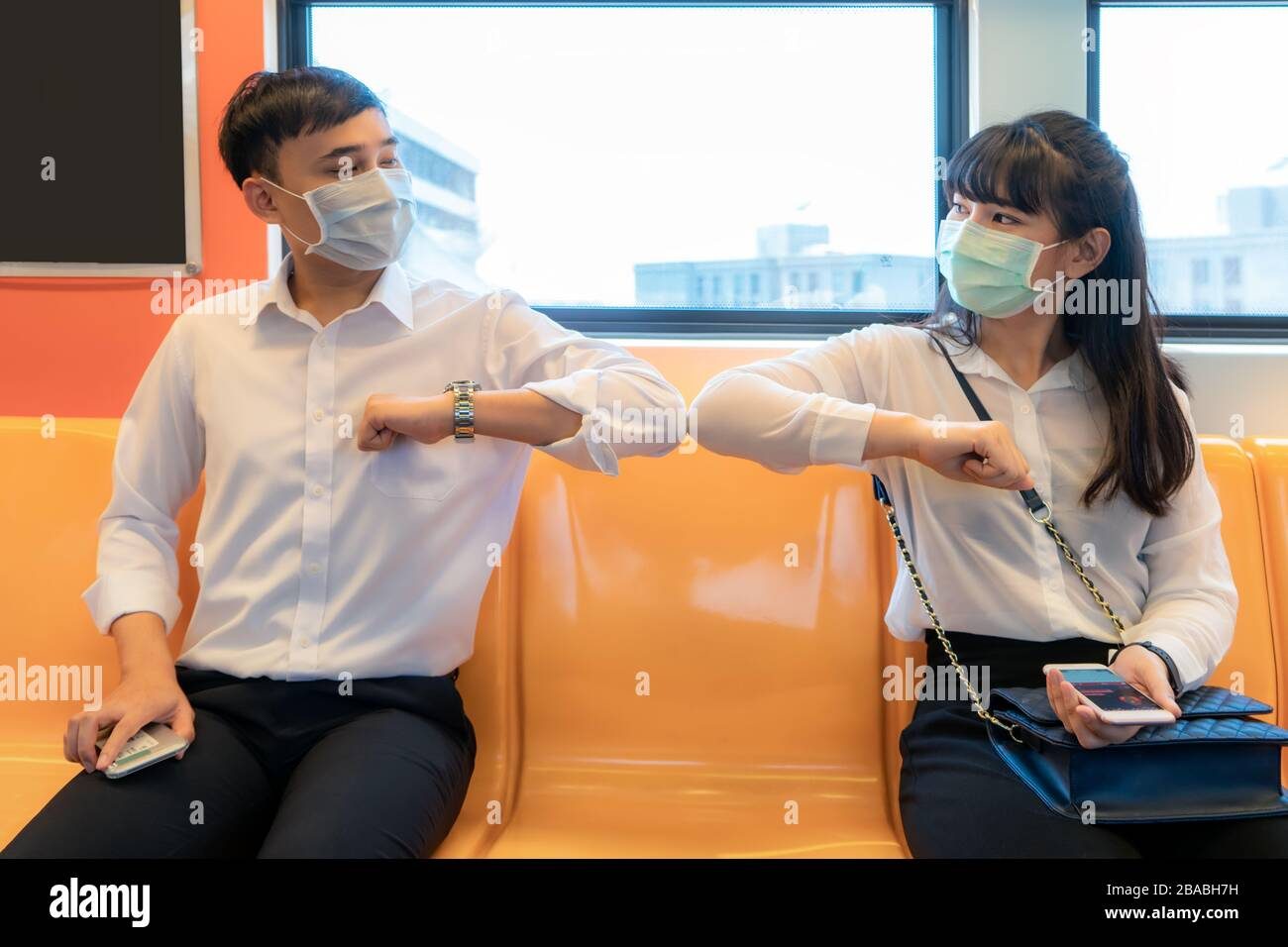 Elbow bump is new novel greeting to avoid the spread of coronavirus. Two Asian business friends meet in subway. Instead of greeting with a hug or hand Stock Photo