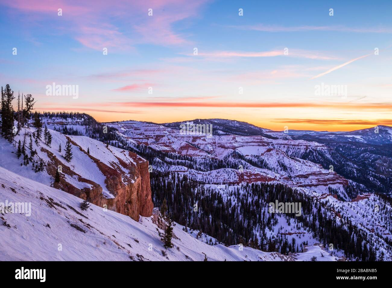 Pink and orange colorful clouds overhead at sunset. Below, orange and red rock covered in snow in Southern Utah winter scene. Stock Photo