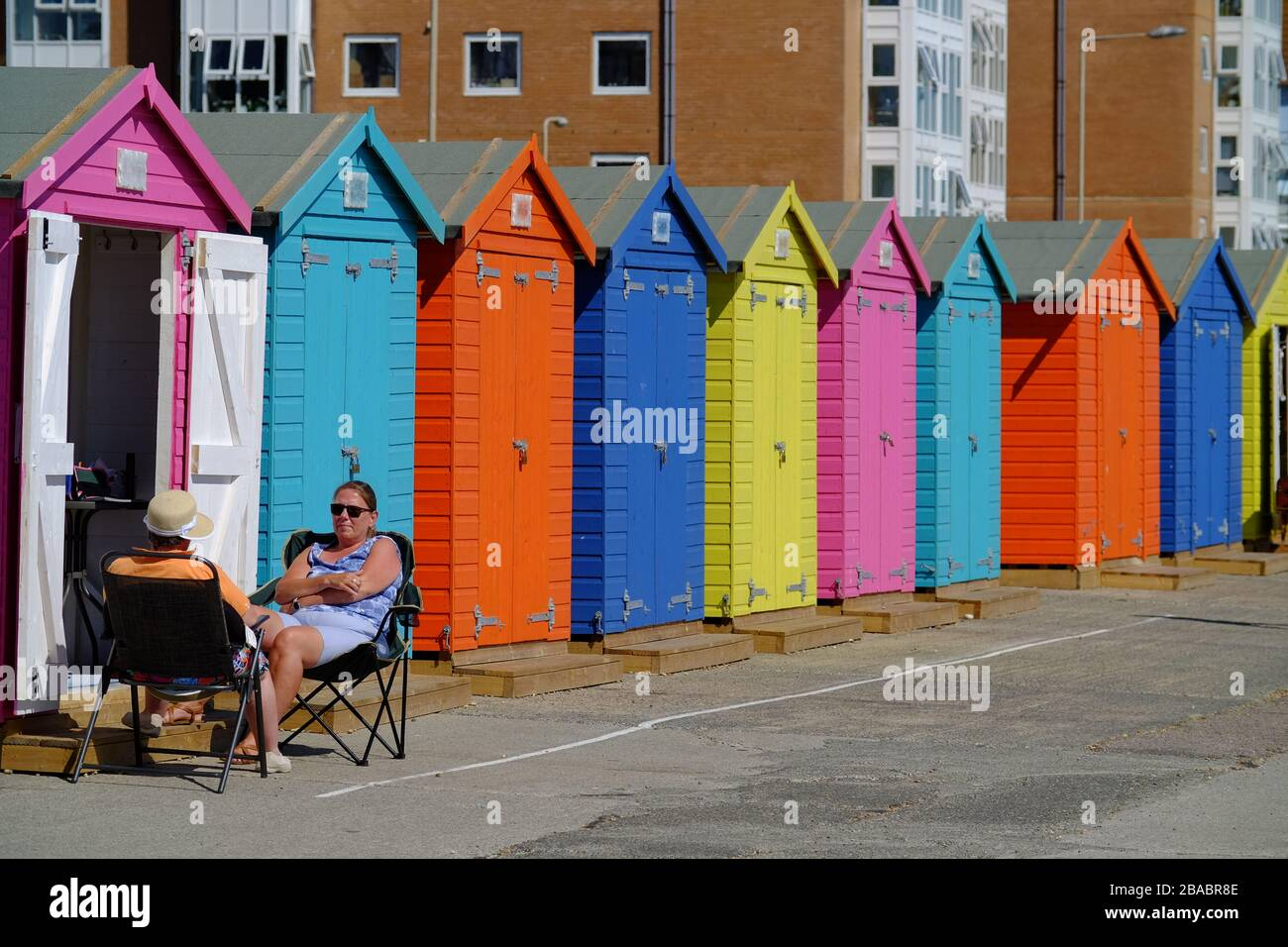 Couple relaxing by colourful beach huts, Seaford, UK Stock Photo