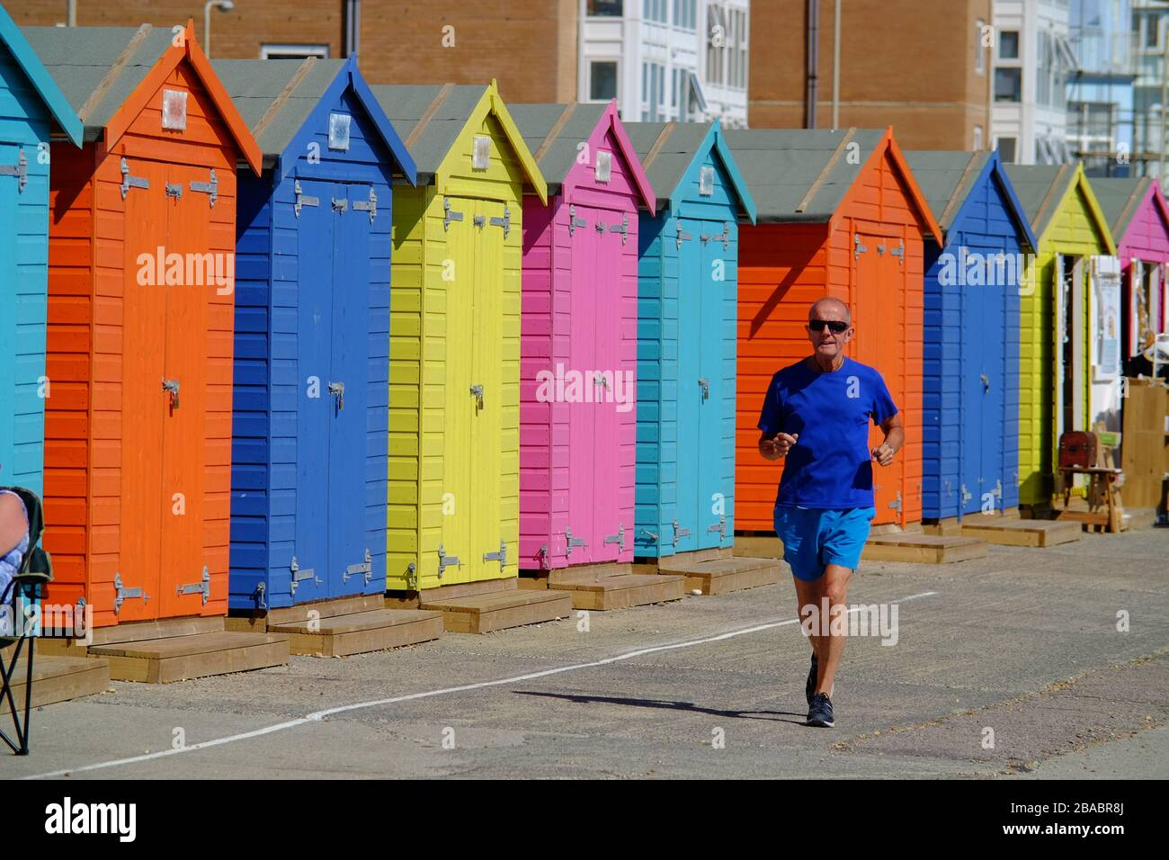 Older man jogging along a seafront by colourful beach huts. Seaford, UK Stock Photo