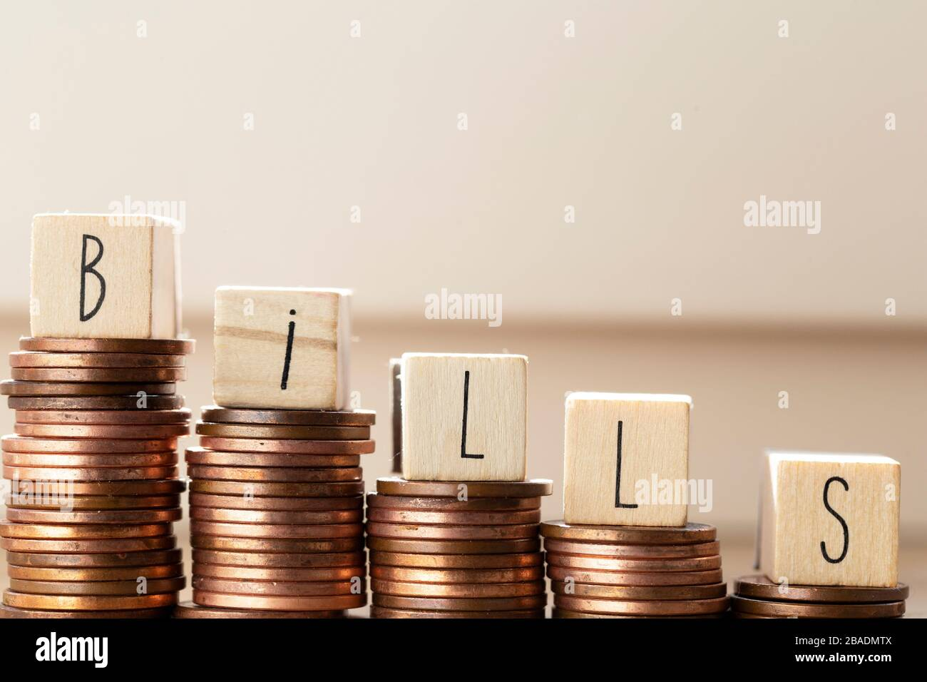 Wooden blocks with the word bills and pile of coins, money climbing stairs Payment of taxes and of debt to the state. Concept of financial crisis and Stock Photo