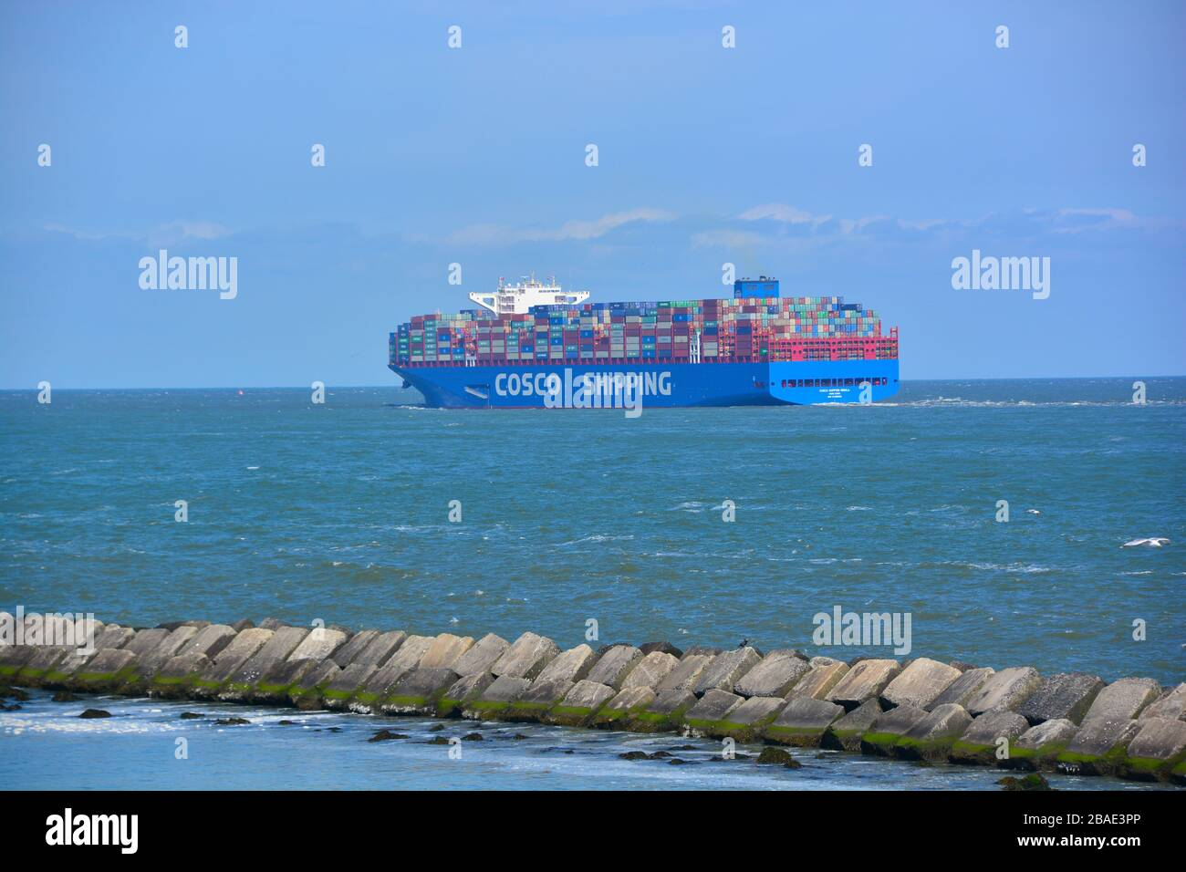 Rotterdam, The Netherlands-September 2019; wide angle view of a large containership arriving in Rotterdam port with the large breakwater concrete ston Stock Photo