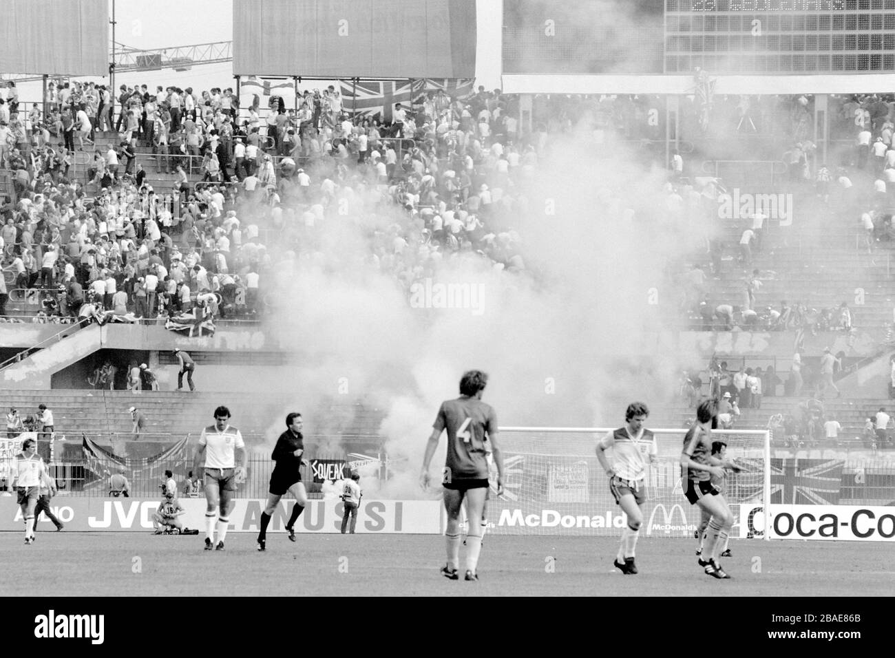 Clouds of tear gas rise from the terraces behind the England goal as Italian riot police try to control the hooligan element amongst the England following Stock Photo