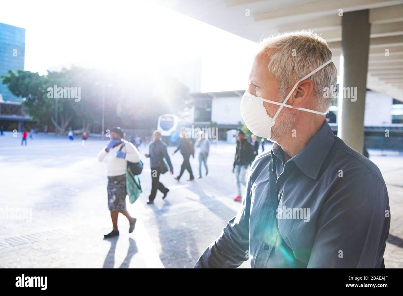 Middle aged man wearing coronavirus Covid 19 mask on the go Stock Photo