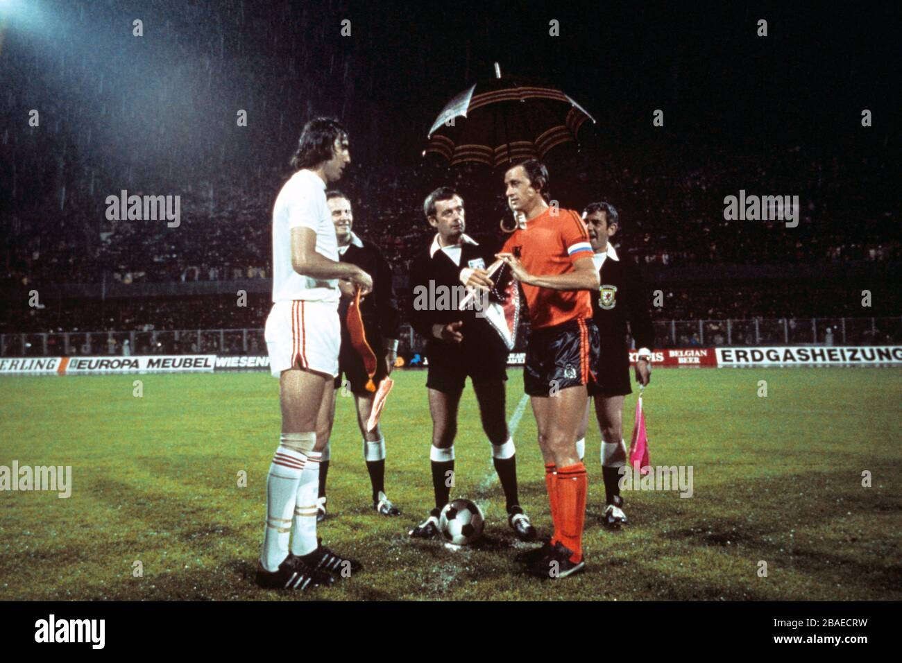 Referee Clive Thomas (c) holds an umbrella over Holland captain Johan Cruyff (r) as he exchanges pennants with Czechoslovakia captain Anton Ondrus (l) before the match Stock Photo