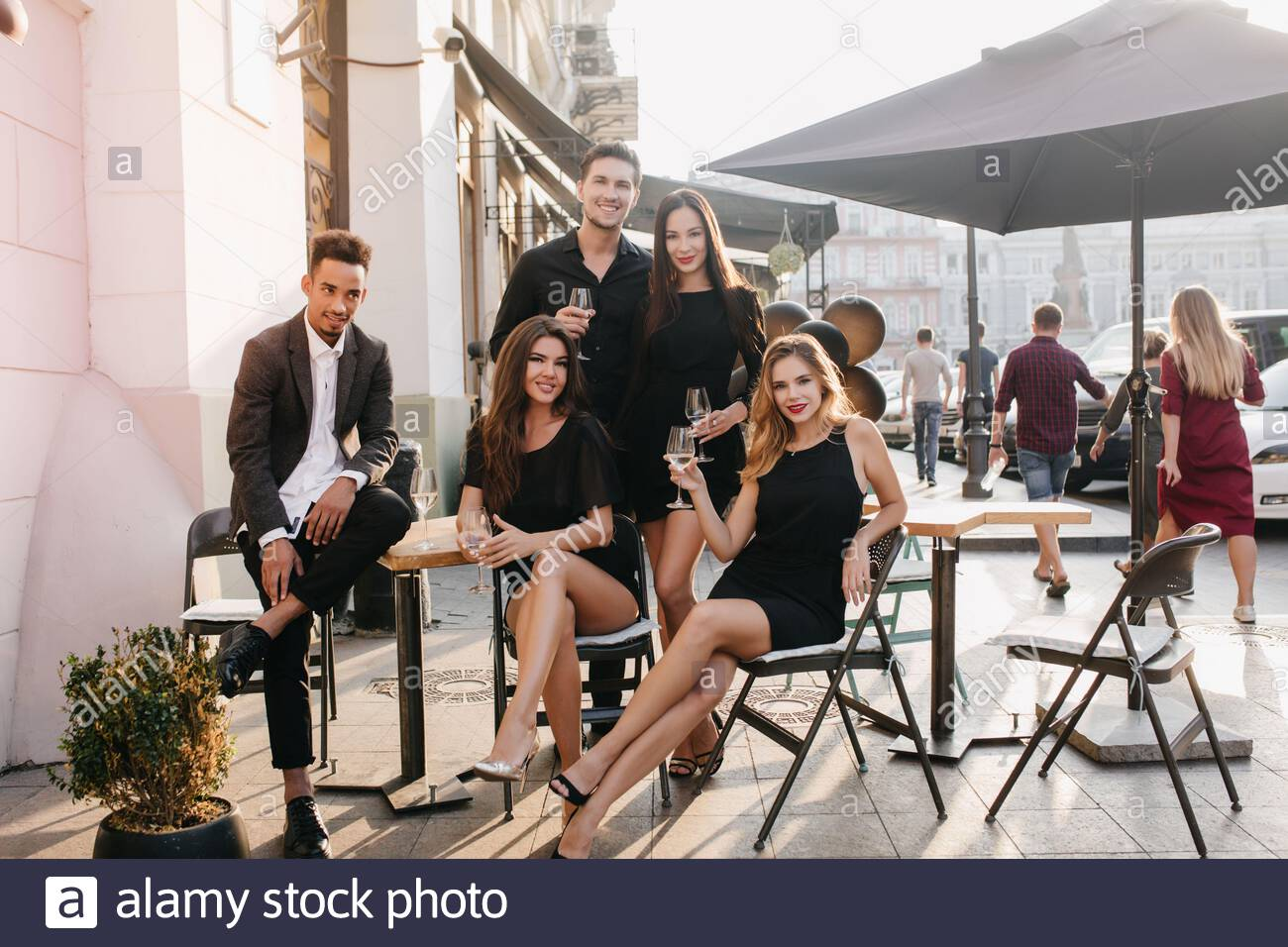 Stylish African Man Sitting In Confident Pose And Looking At Girls In Outdoor Cafe Portrait Of Happy Couple Posing On The Street With Friends Enjoying Meeting Stock Photo Alamy