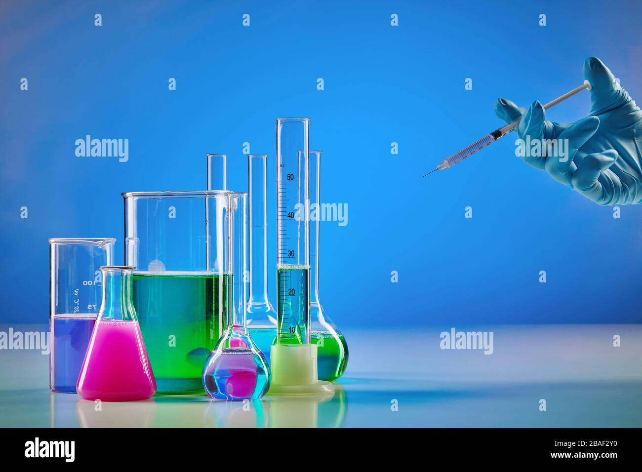 Hand in disposable glove holding syringe. Colorful chemical reagents in beakers, medical flasks and measuring cylinder, blue background. Coronavirus, Stock Photo