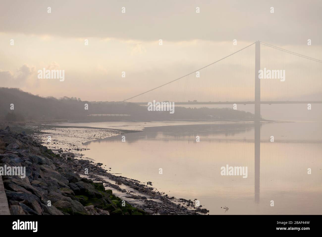 LNER High speed train passing the Humber bridge and river Humber at North Ferriby on a misty morning with a hull - Kings cross train Stock Photo
