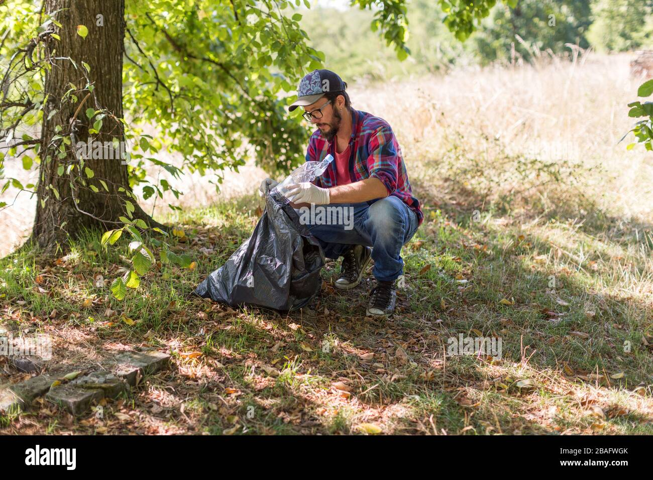 Young man picking up litter in his local park Stock Photo