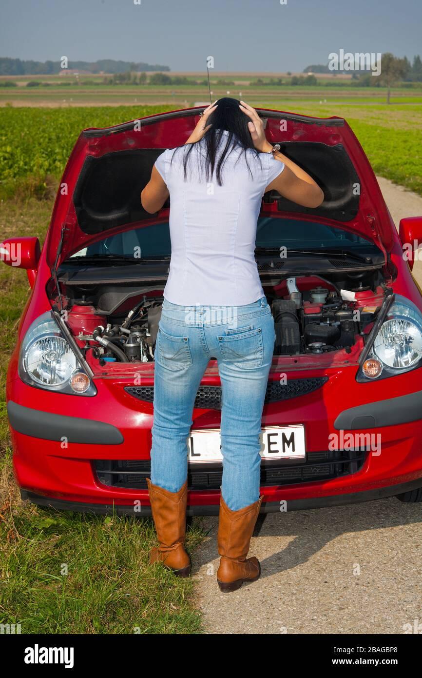 Junge Frau hat eine Autopanne, Motorschaden,  MR: Yes Stock Photo