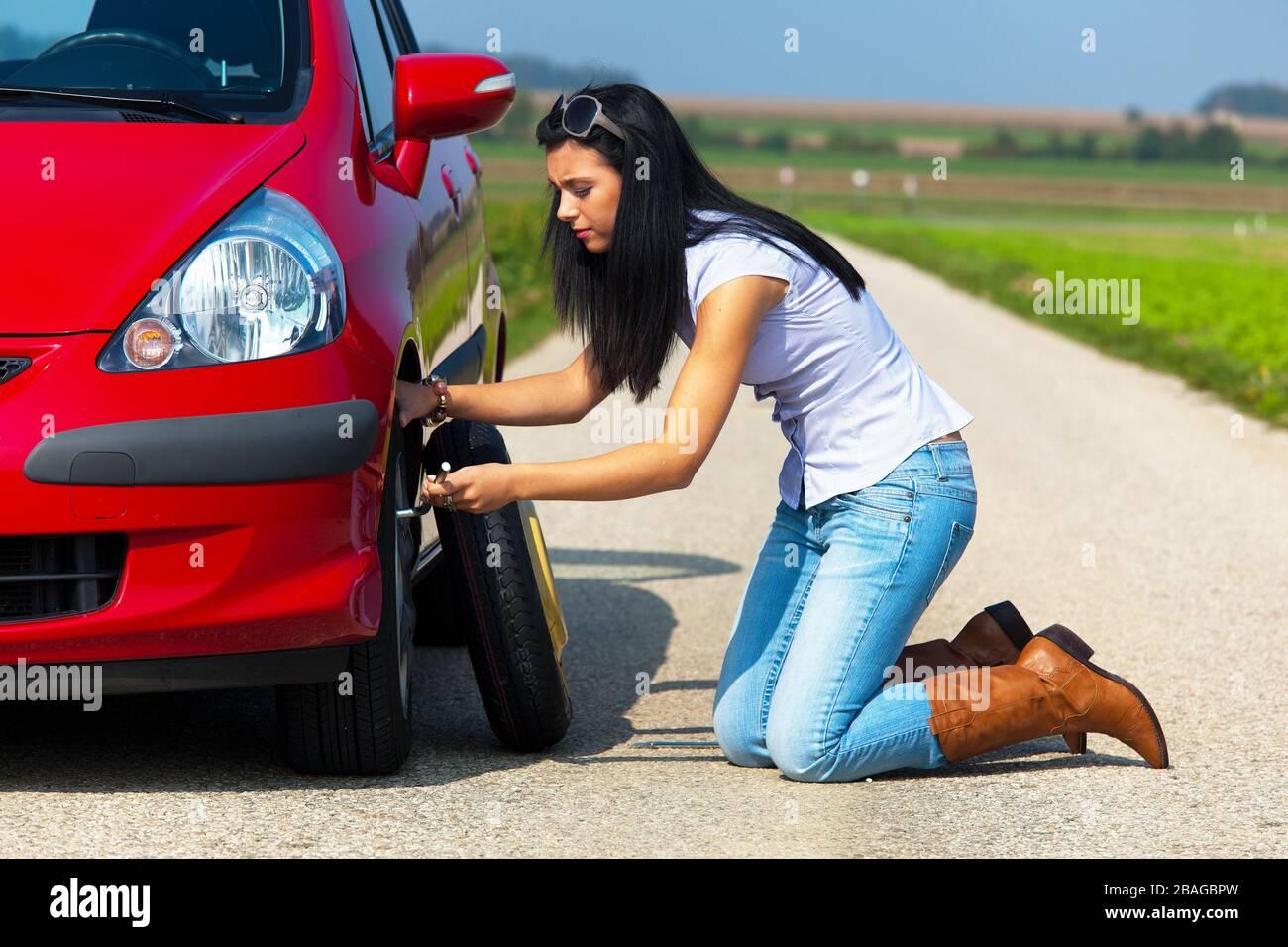 Junge Frau hat eine Autopanne und wechselt einen Reifen, Reifenwechsel, MR: Yes Stock Photo