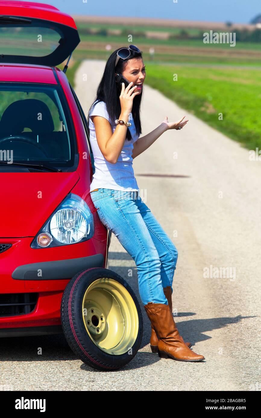 Junge Frau hat eine Autopanne, Reifenwechsel, telefoniert um Hilfe, MR: Yes Stock Photo