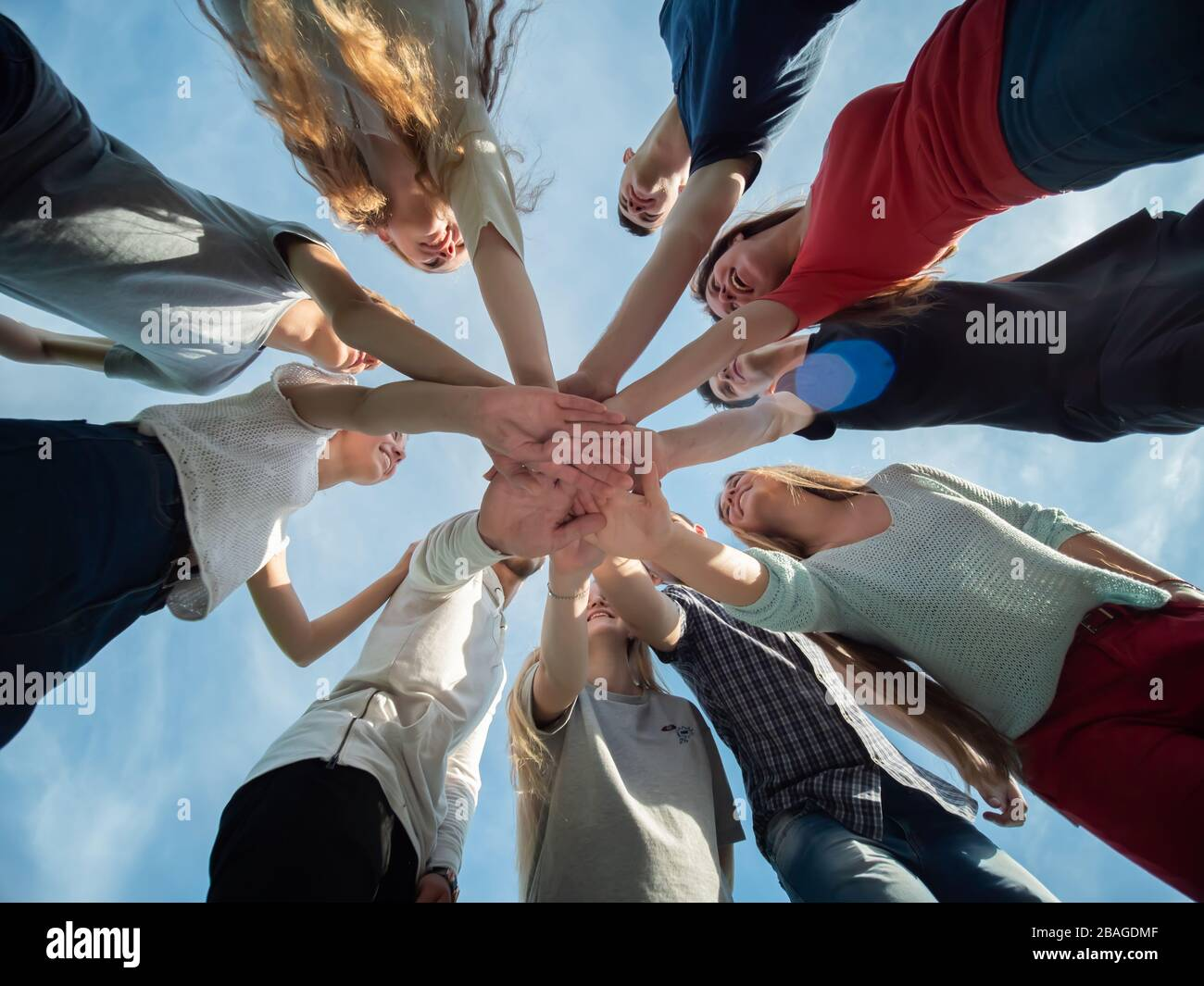 A friendly company of friends join hands as a sign of joint business. Stock Photo