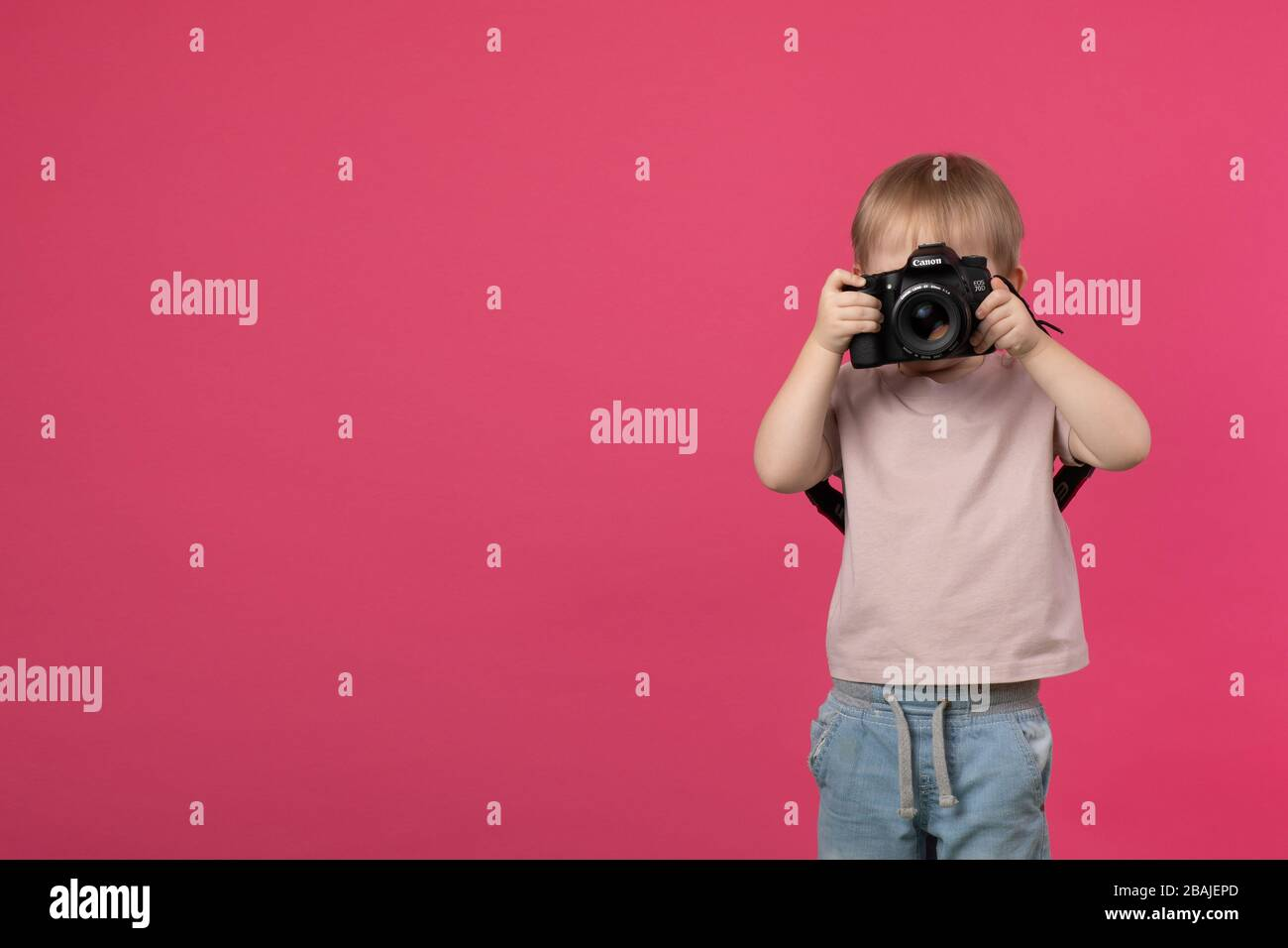 SAINT-PETERSBURG, RUSSIA - MARCH 22, 2020: A child boy stands and holds in his hands a Canon 70d camera with a lens with an EF 50mm 1.4 mount and take Stock Photo