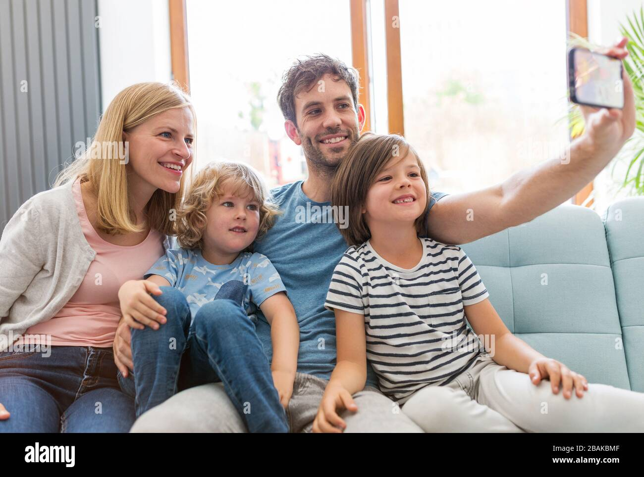 Happy young family with two children at home Stock Photo