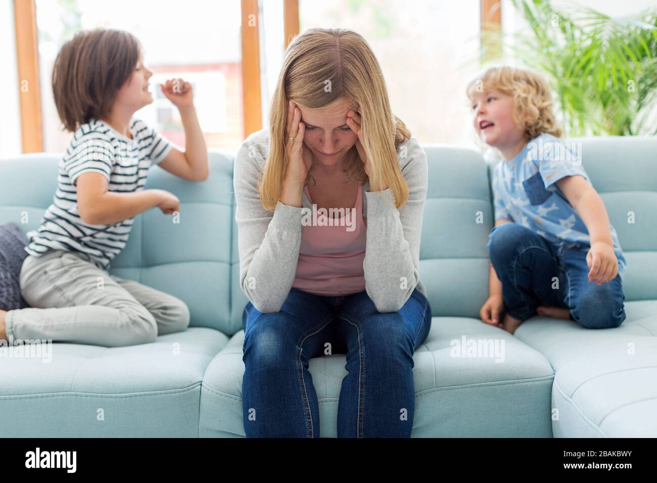 Mother with headache and children jumping on sofa Stock Photo