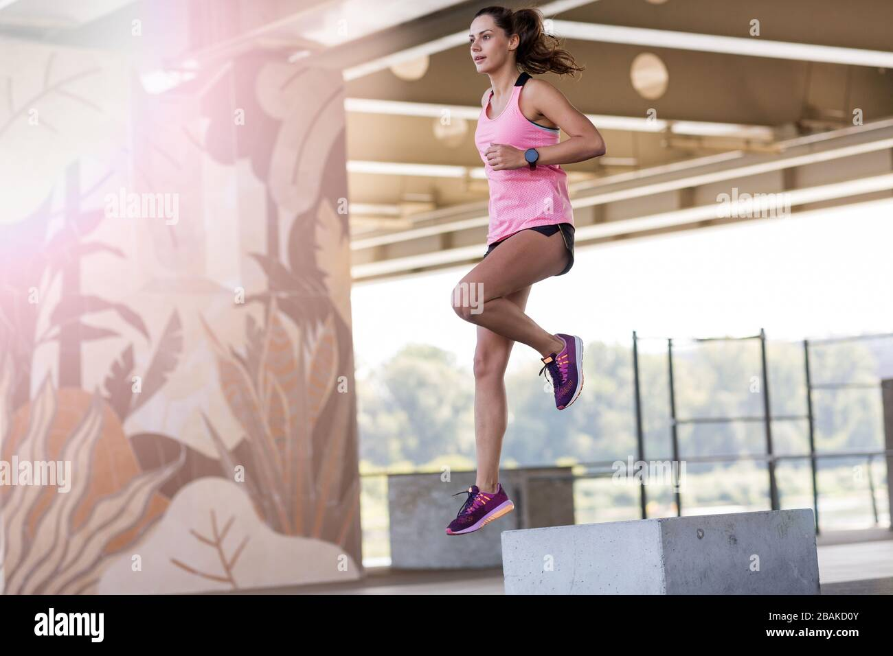 Young woman doing fitness exercise in urban area Stock Photo