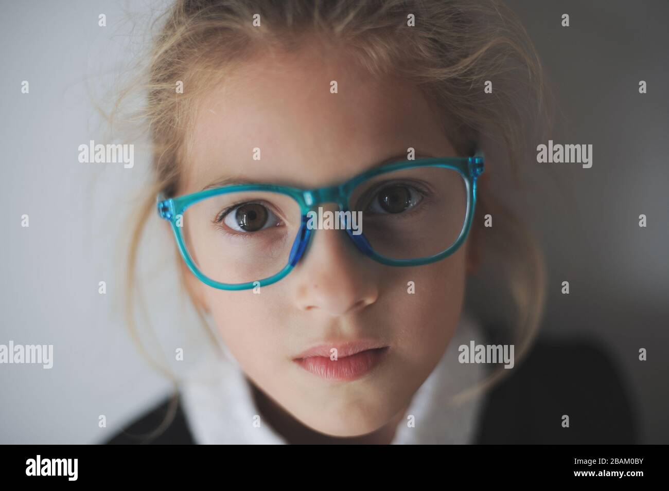 beautiful little sad girl in blue glasses Stock Photo