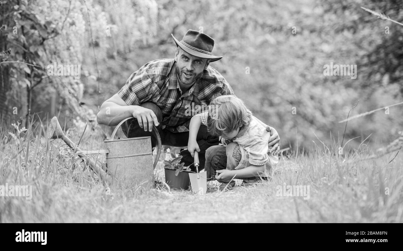 Growing plants. Take care of plants. Boy and father in nature with watering can. Gardening tools. Planting flowers. Dad teaching little son care plants. Little helper in garden. Make planet greener. Stock Photo