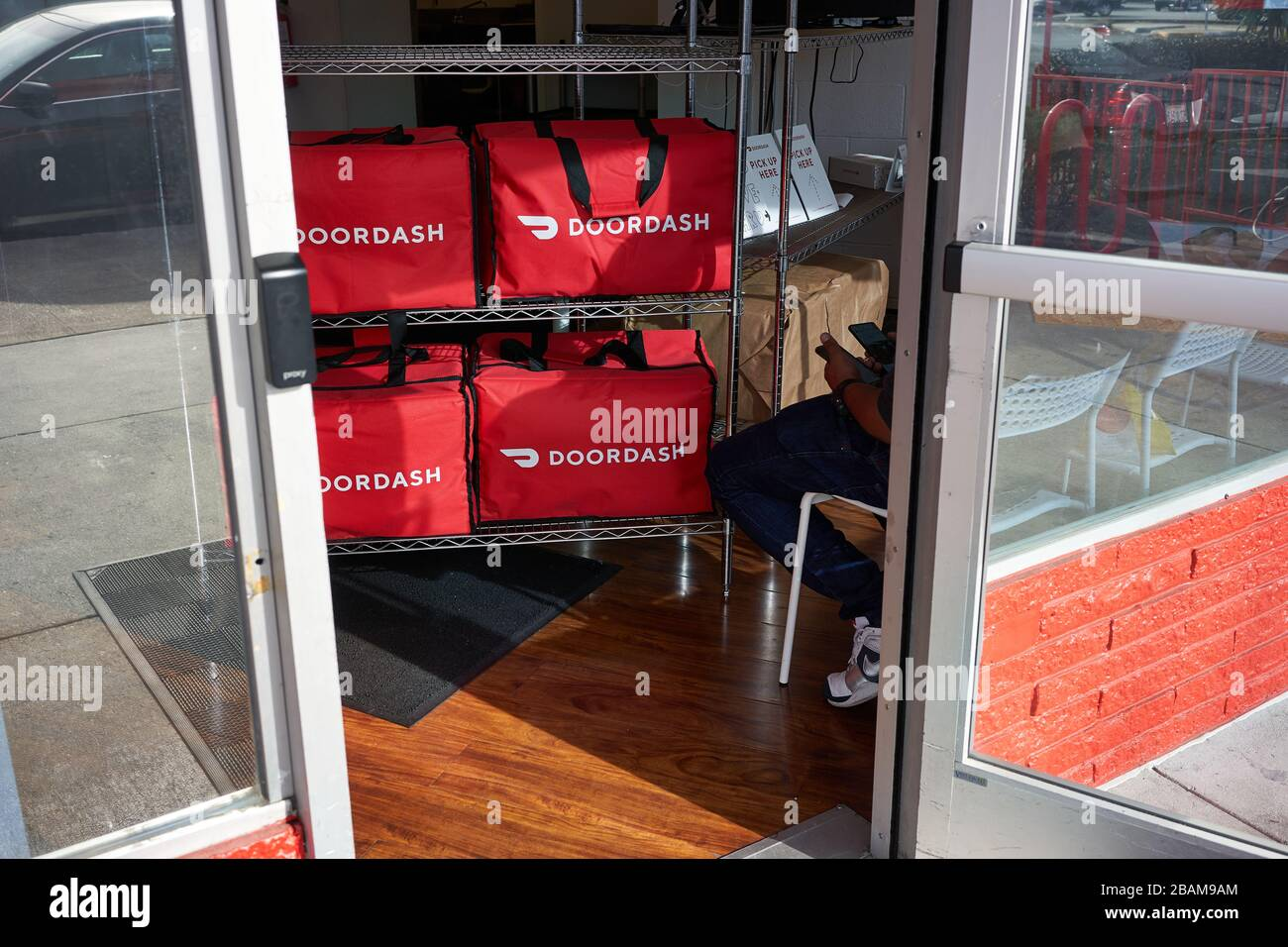 A DoorDash delivery worker checks his phones at the DoorDash Kitchens location in Redwood City, California. Stock Photo