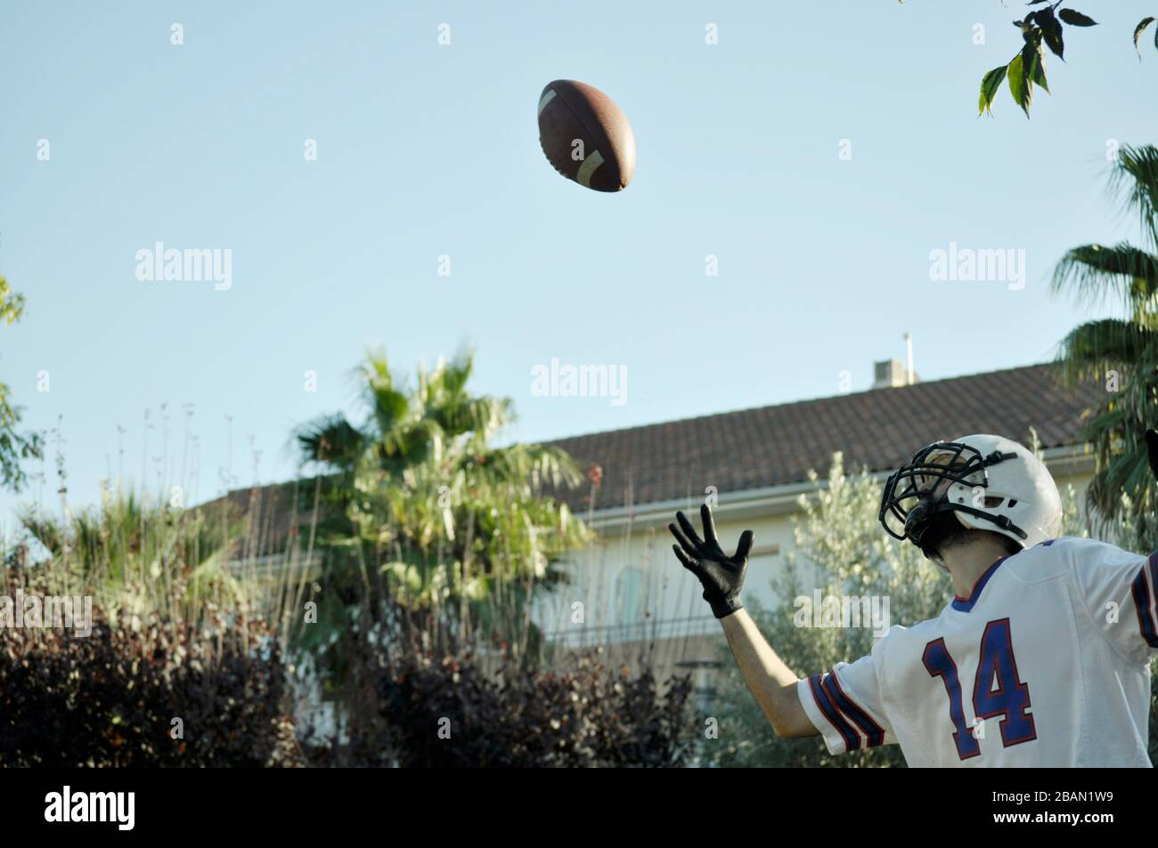 American football player in a game. Player catching an American football ball in a park. Stock Photo