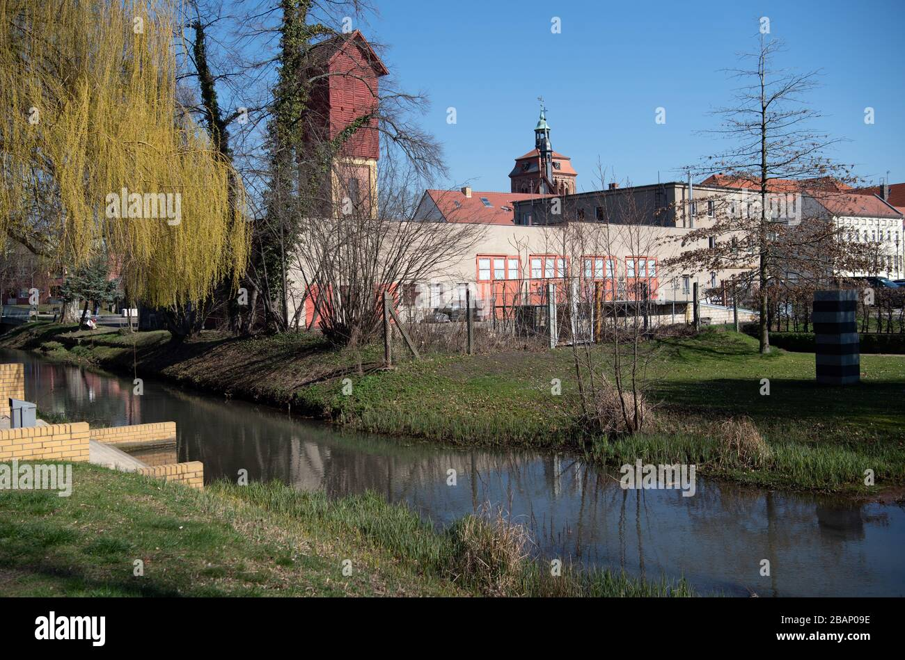 Luckenwalde, Germany. 24th Mar, 2020. The Nuthepark with the corresponding Nuthe. In the background you can see the towers of St. Johannis and Marktirche. The water has its source in Niedergörsdorf in Brandenburg and flows into the Potsdam Havel after about 60 kilometres. Credit: Soeren Stache/dpa-Zentralbild/ZB/dpa/Alamy Live News Stock Photo