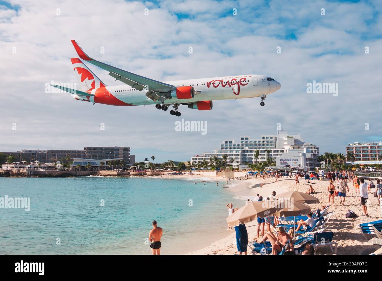 An Air Canada Rouge Boeing 767 comes in to land over tourists on Maho Beach, St. Maarten Stock Photo