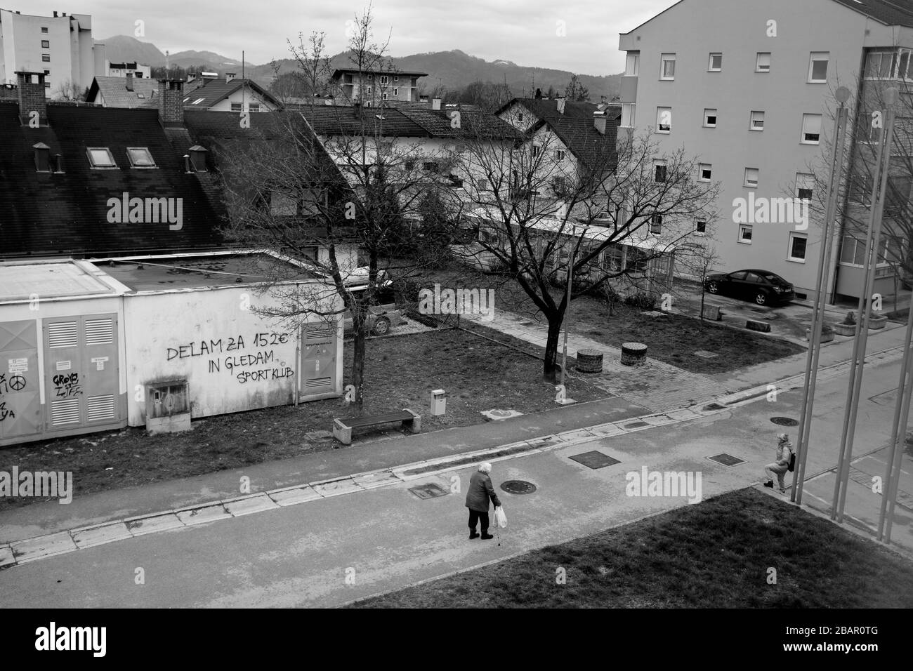 Kranj, Slovenia, March 22, 2020: Two elderly women speak to each other on the street maintaining a large distance in accordance with social distancing rules during the coronavirus outbreak nationwide lockdown. Stock Photo