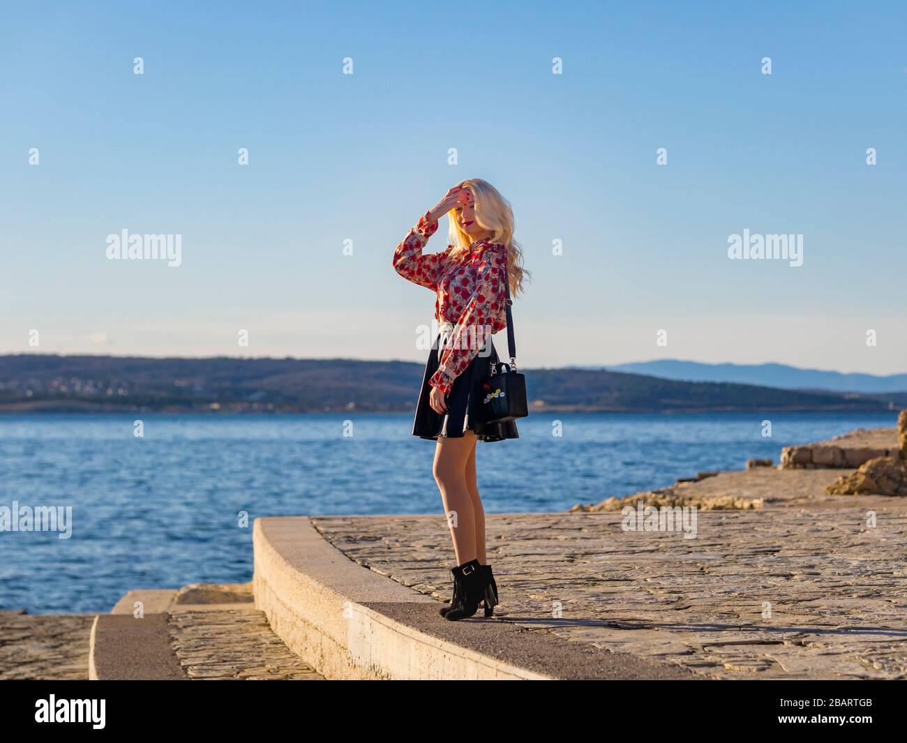 Curious standing on seaside promenade near sea profile sideview side-view looking at camera eyeshot hand holding touching hair flirting flirt Stock Photo