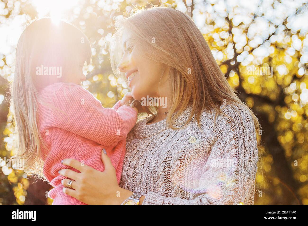 Closeup of happy young family spending time together outdoors. Young mother holding her little daughter in hands and hugging her while standing in aut Stock Photo
