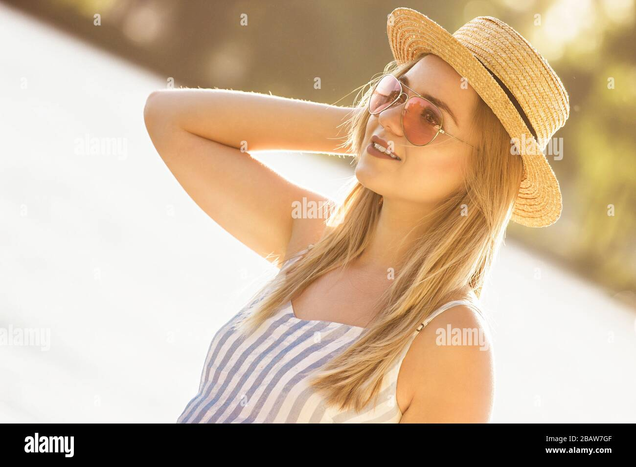 Portrait of tender young woman in straw hat and sunglasses standing at sunny riverside. Beautiful stylish girl in stripped overalls posing at beach on Stock Photo
