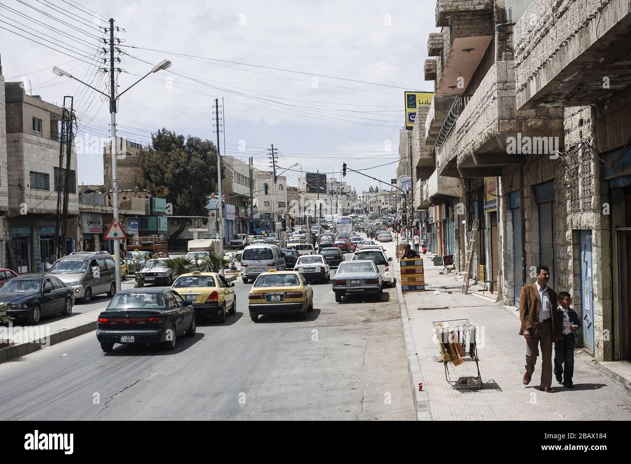 Madaba, Jordan, May 1, 2009: Heavy traffic in the street of Madaba, Jordan, and a man and a boy walking on the sidewalk. Stock Photo