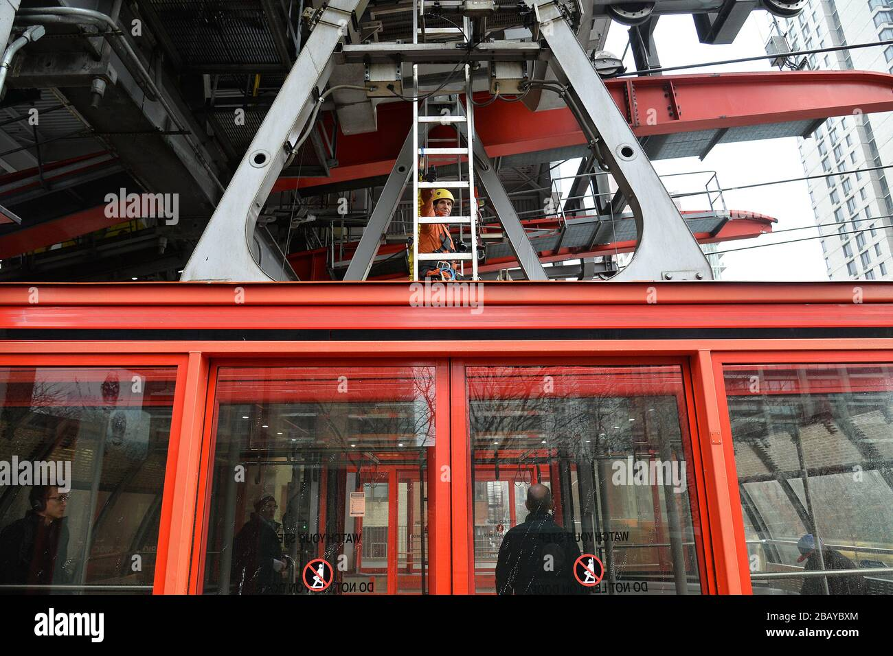 New York City, USA. 29th Mar, 2020. Attached by a safety harness, a maintenance worker rides atop the Roosevelt Island Tram, making several trips between Manhattan and Roosevelt Island during his inspection, New York, NY, March 29, 2020. (Anthony Behar/Sipa USA) Credit: Sipa USA/Alamy Live News Stock Photo