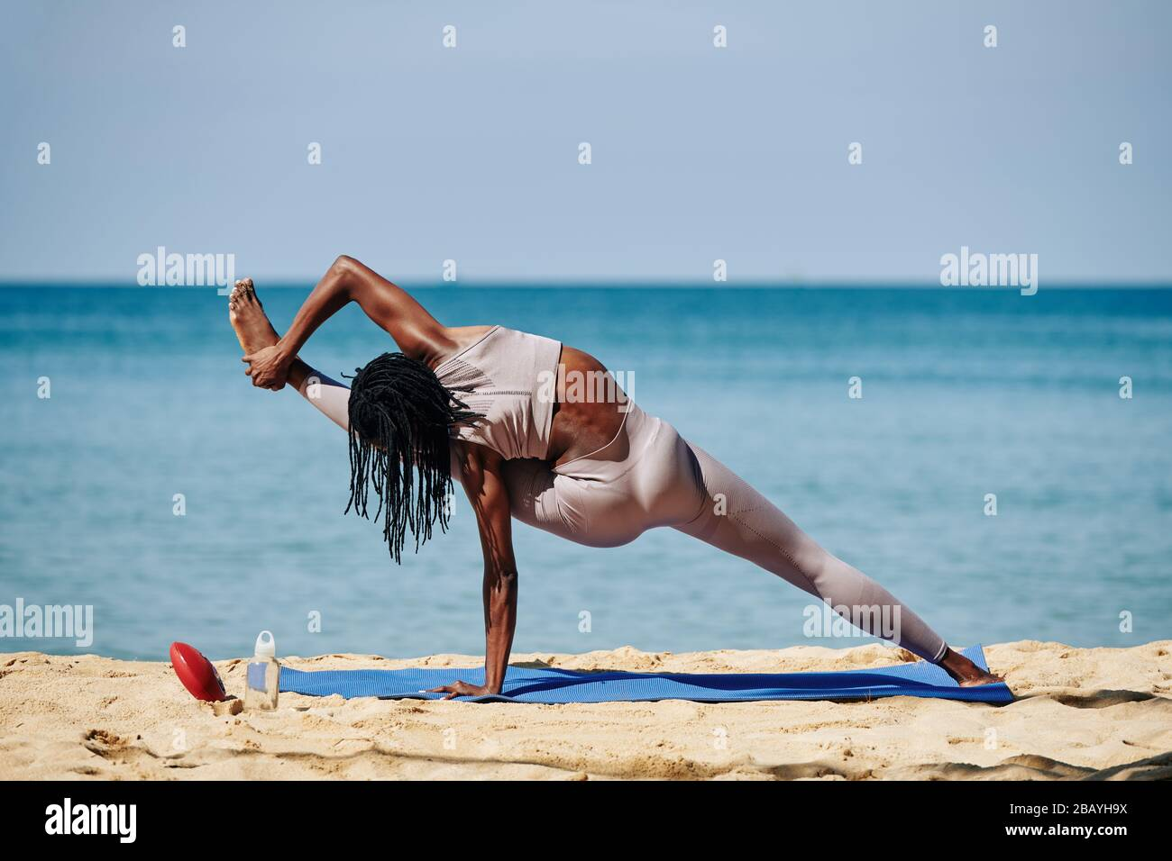 Fit stong young woman doing Visvamitrasana, she is extending leg out to the side and catch hold of foot with hand Stock Photo