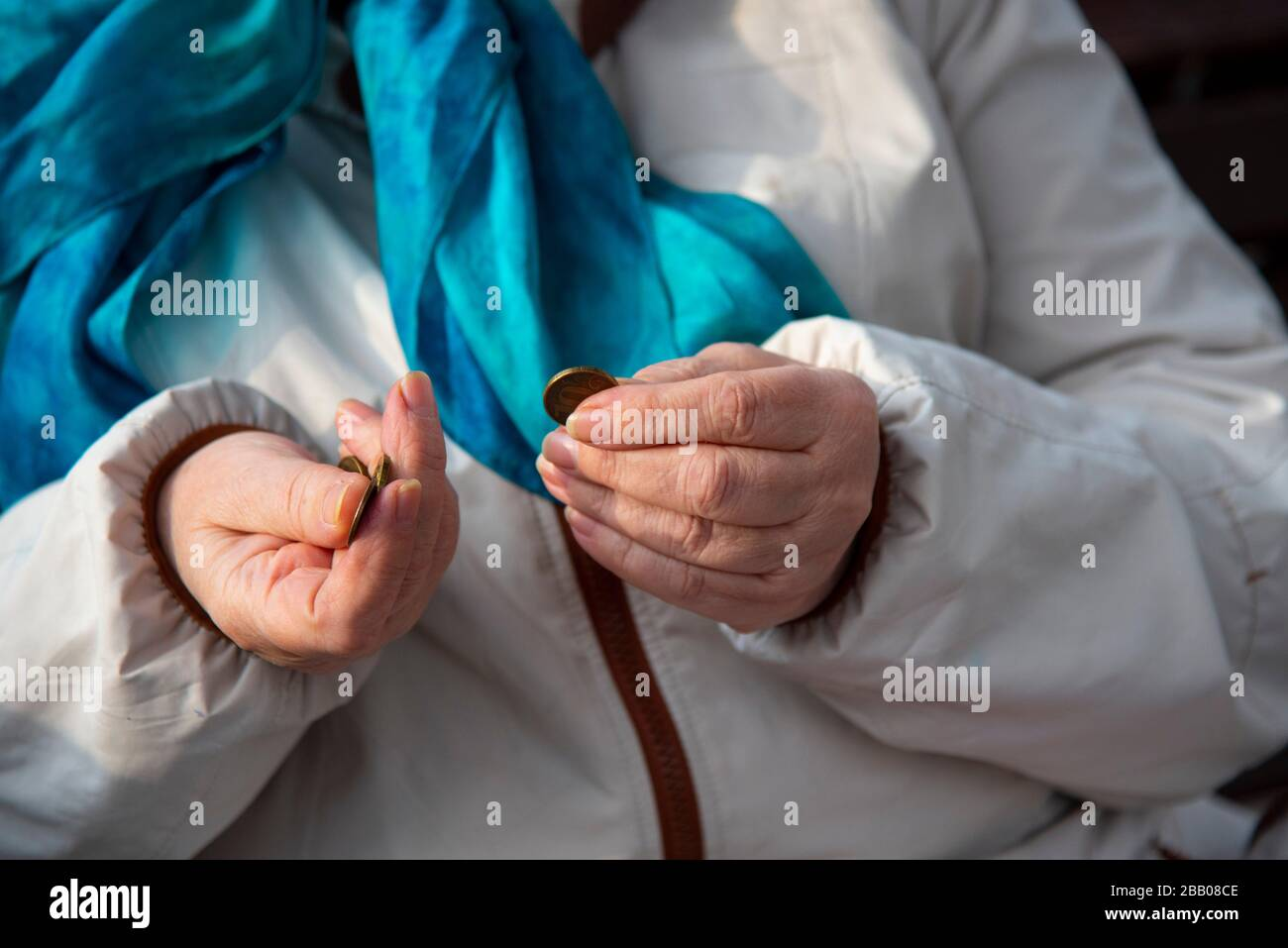 The wrinkled Hands of an old woman sorting through small coins. Stock Photo