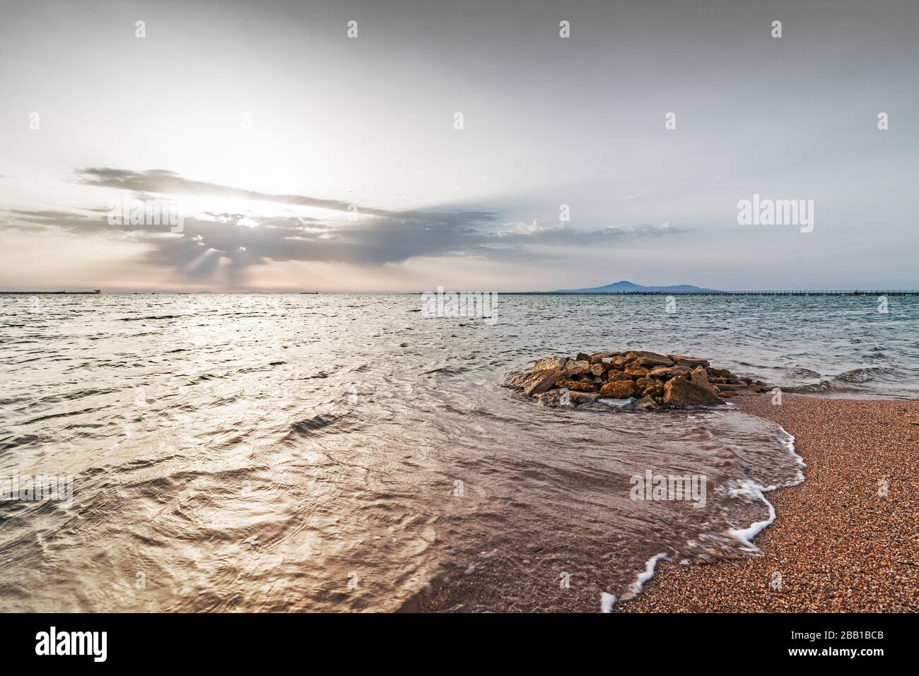 Sea shore at dawn. Seawater finds on stones of different size and color. Light wave and swell on the surface of the water. Red Sea, Sharm El Sheikh, E Stock Photo