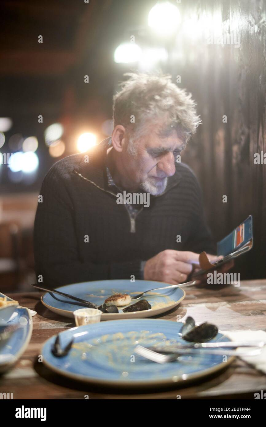 Friesian senior man checking phone in restaurant after having fish for dinner. Stock Photo