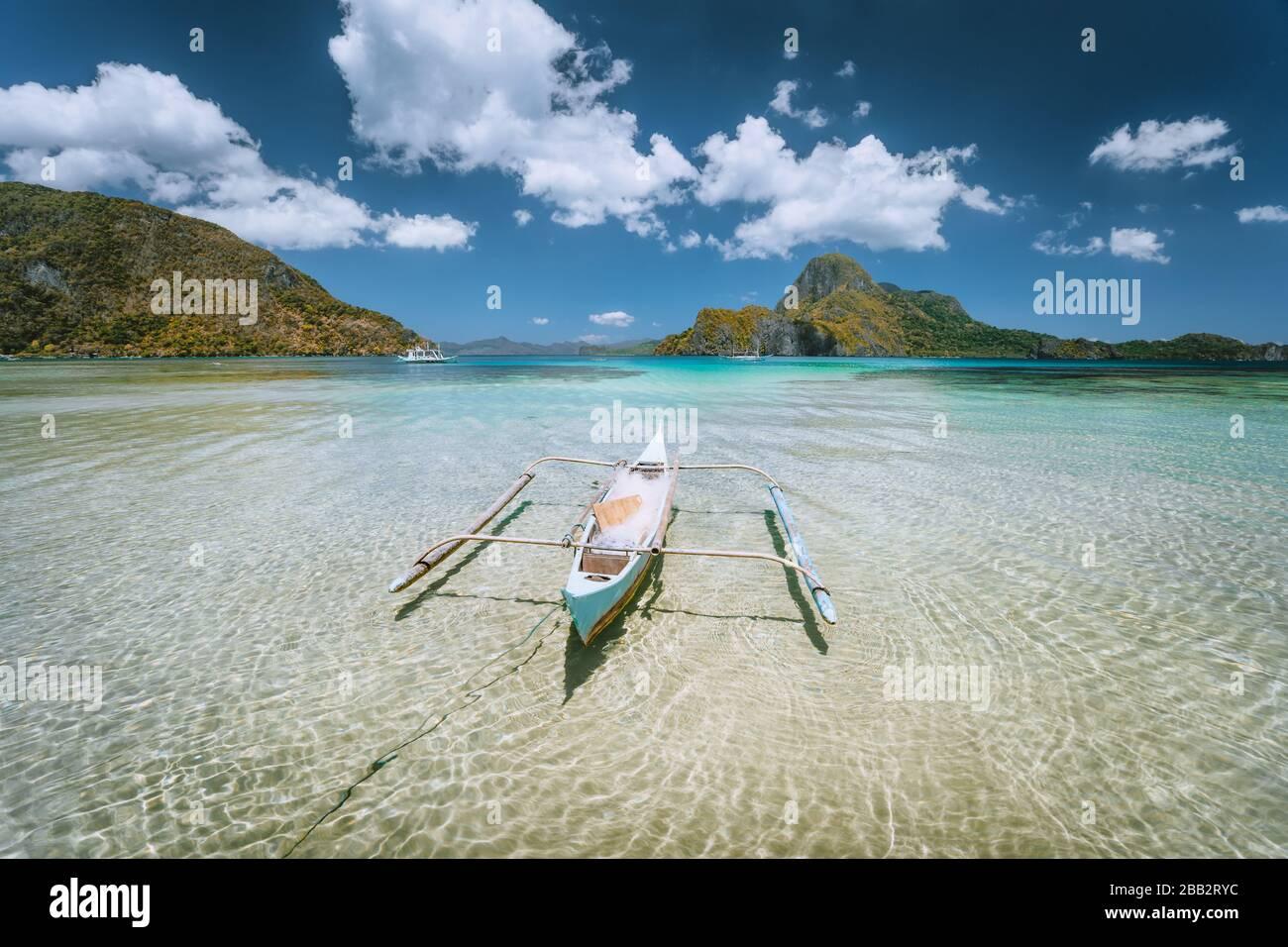 El Nido bay. Palawan island, Philippines. Lonely filippino fishing boat in shallow water lagoon at noon. Travel exotic Stock Photo