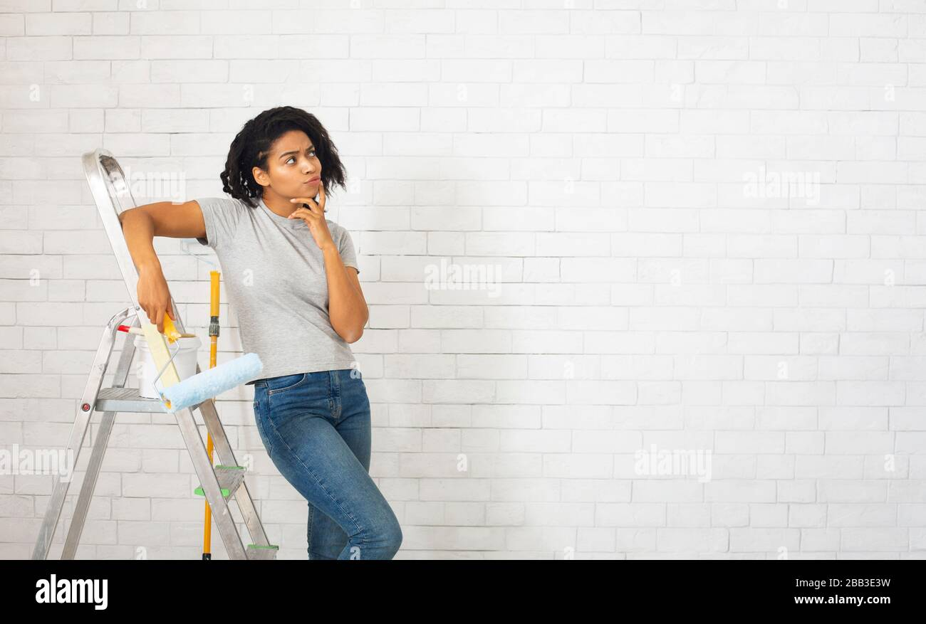 Millennial woman with stepladder thinks about repair Stock Photo