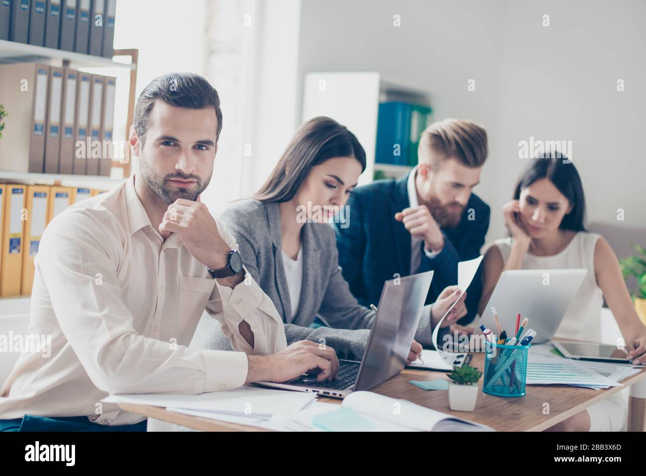 Close up of young business people in formal wear discussing something seriously while sitting together at the table in light modern workplace Stock Photo