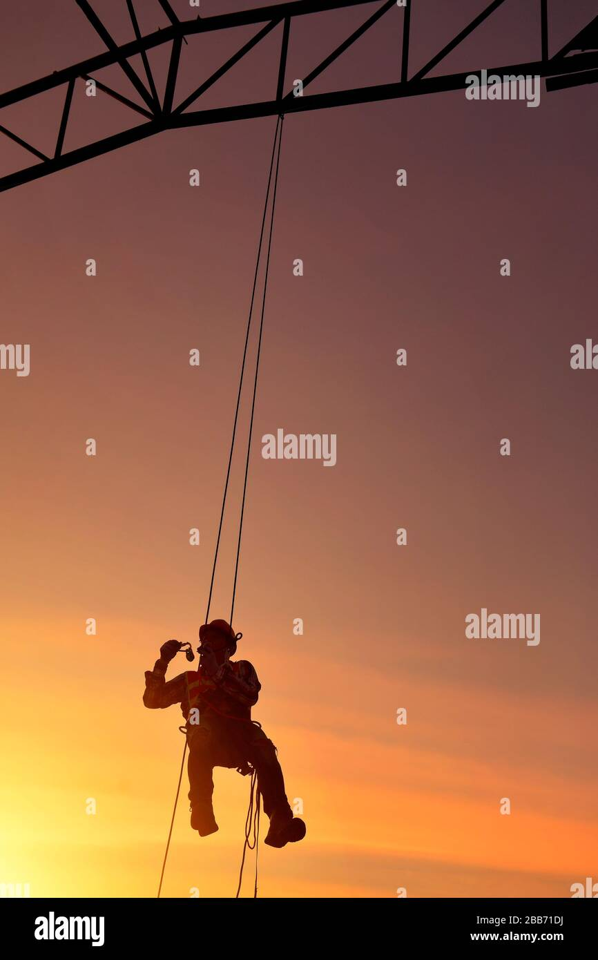 Silhouette of a construction worker hanging on safety harness on a construction site, Thailand Stock Photo