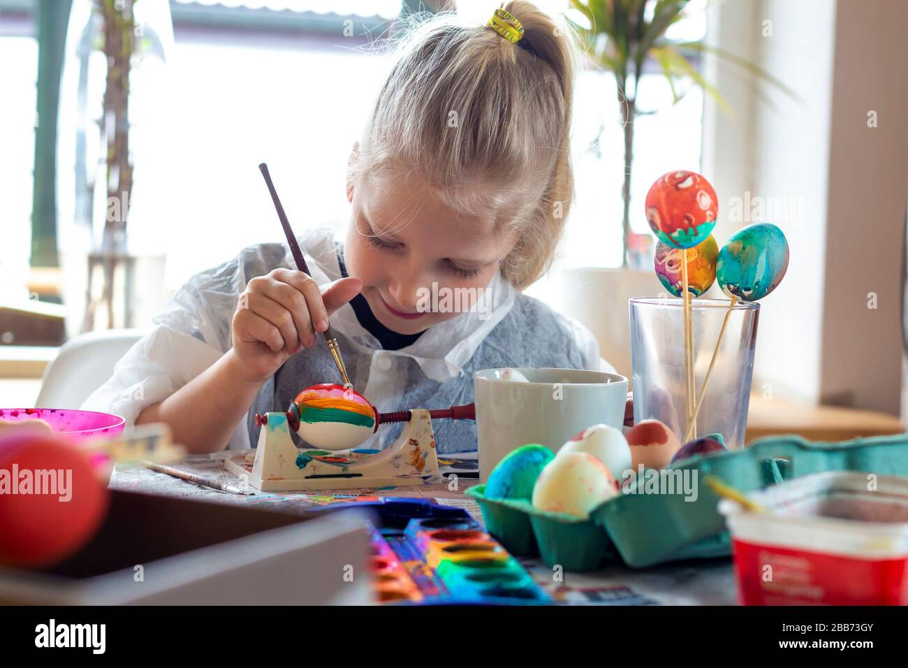 Portrait of adorable blonde girl at home painting easter eggs Stock Photo