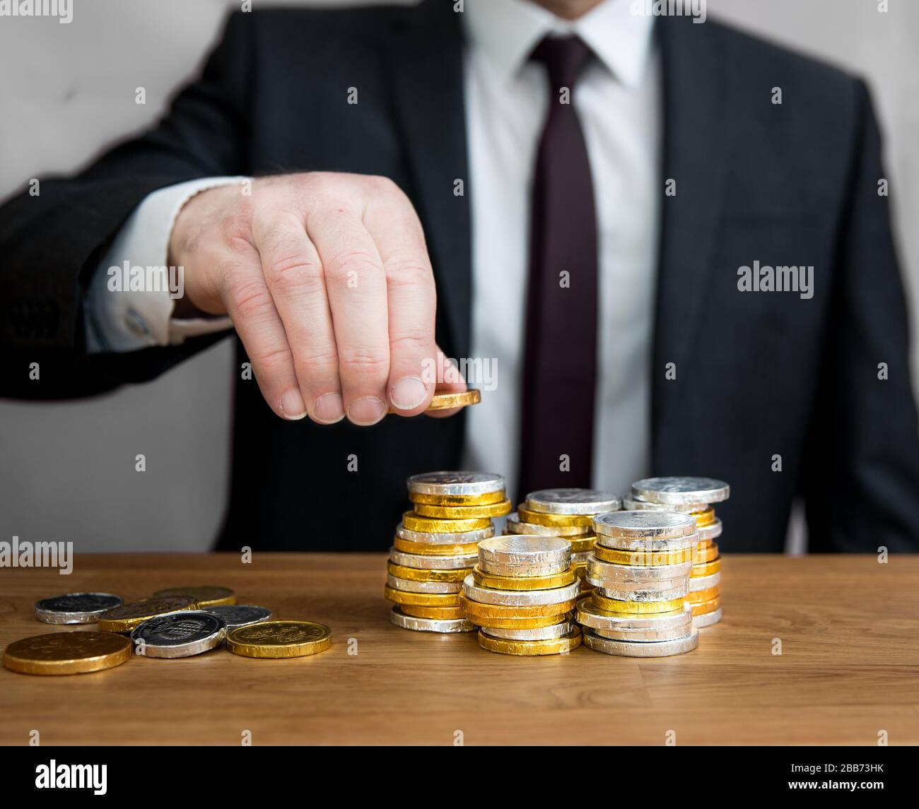A midsection concept of a businessman with a large amount of cash counting coins into stacks to add up corporate profit and assets. Stock Photo