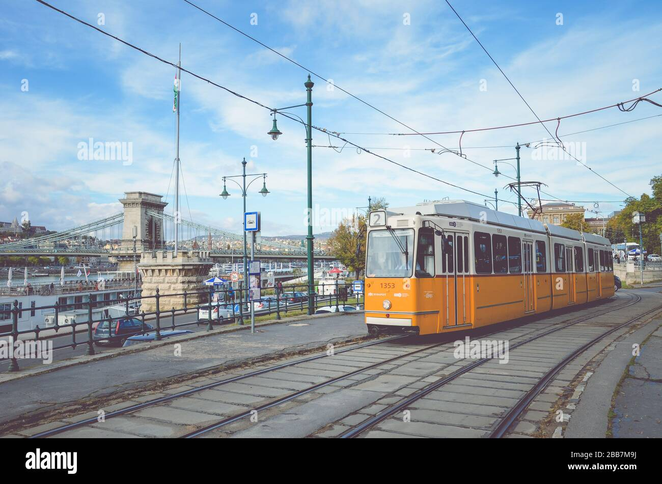 Budapest, Hungary - Nov 6, 2019: Yellow tram at a tram station. Szechenyi chain bridge and the historical center in the background. Hungarian public transport. Horizontal photo with filter. Stock Photo