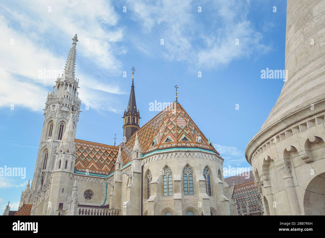 The spire of the famous Matthias Church in Budapest, Hungary. Roman Catholic church built in the Gothic style. Orange colored tile roof. Blue sky and white clouds above. Horizontal photo with filter. Stock Photo
