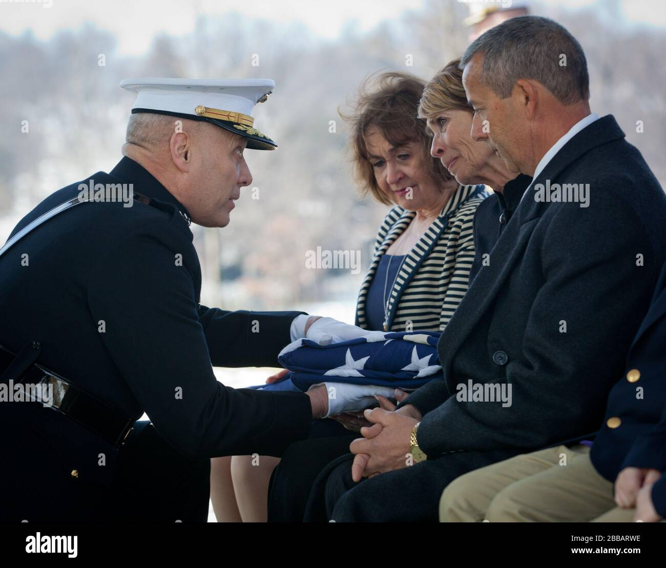 """""""The Assistant Commandant of the Marine Corps, Gen. John M. Paxton, Jr., his wife Debbie, and Mrs. Bonnie Amos attend the funeral service for Retired Colonel Charles Waterhouse at Arlington National Cemetary, Arlington, VA, Feb. 19, 2014. Col. Waterhouse was a combat artist and was seriously injured during the first wave of Iwo Jima. He suffered from sever nerve damage in his left hand but was still able to paint with his right and continued though out his life to paint artwork up until three weeks before he passed away. (U.S. Marine Corps photo by Cpl. Tia Dufour/Released); 19 February 2014, Stock Photo"""