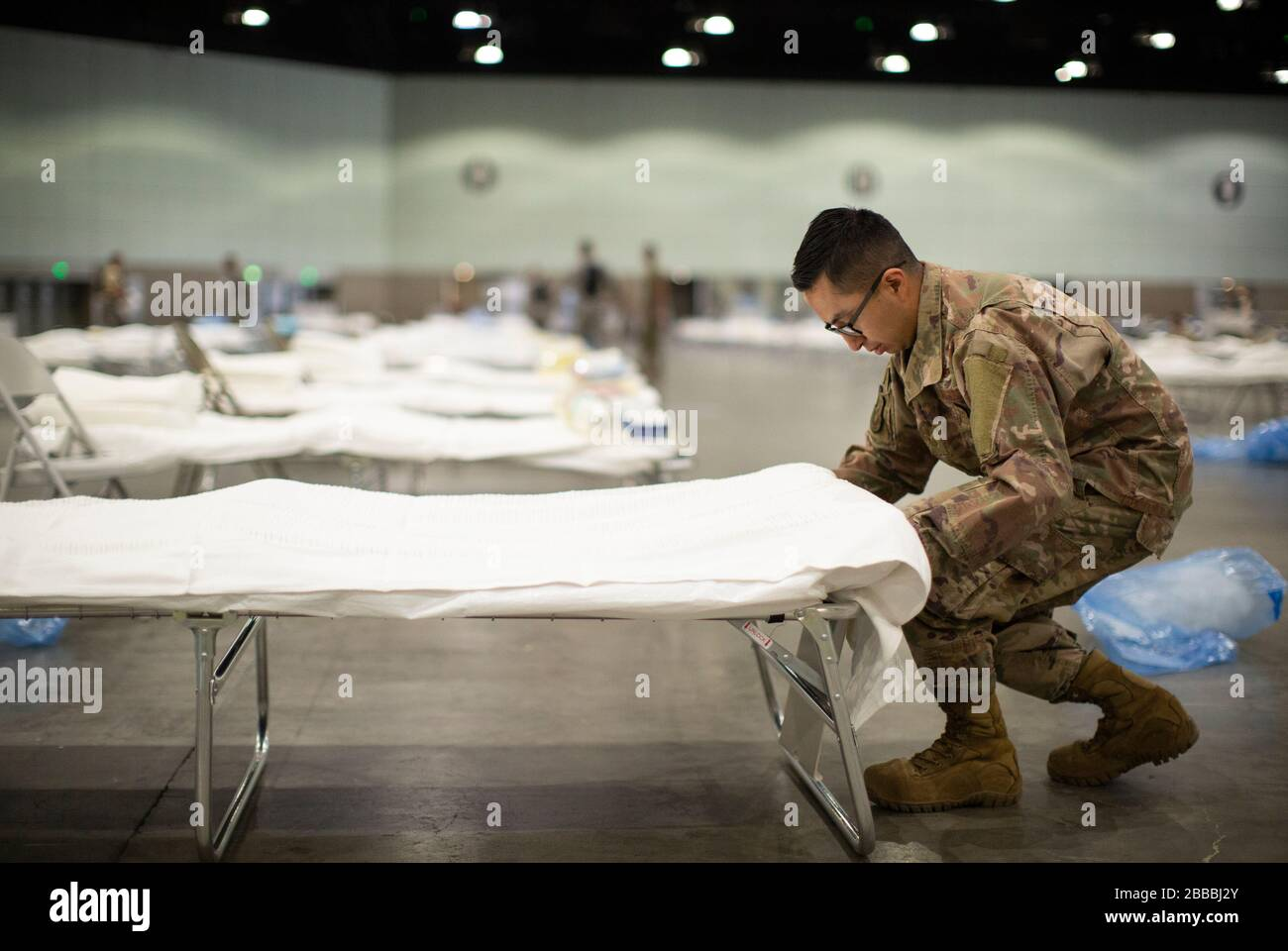 U.S. Air Force Tech. Sgt. Mario Lopez-Casas, a heating, ventilation, air conditioning and refrigeration specialist with the 146th Civil Engineer Squadron in the California Air National Guard's 146th Airlift Wing, puts sheets on a hospital bed while setting up a Federal Medical Station, March 29, 2020, inside the Los Angeles Convention Center as part of California's statewide COVID-19 response effort. This is the third medical station site the Airmen have set up in the state. (U.S. Air National Guard video by Staff Sgt. Crystal Housman) Stock Photo