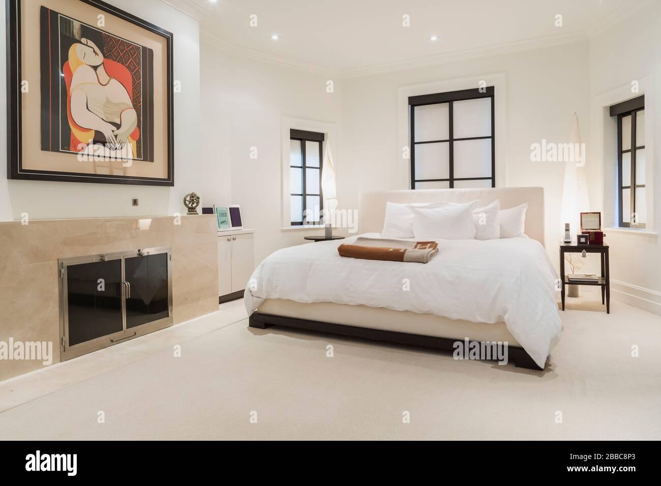 King Size Bed With Cream Coloured Cloth Headboard Wooden Nightstands And Fireplace In Upstairs Master Bedroom With White Carpeting Inside A 1924 Semi Detached Cottage Style Home Quebec Canada This Image Is Property
