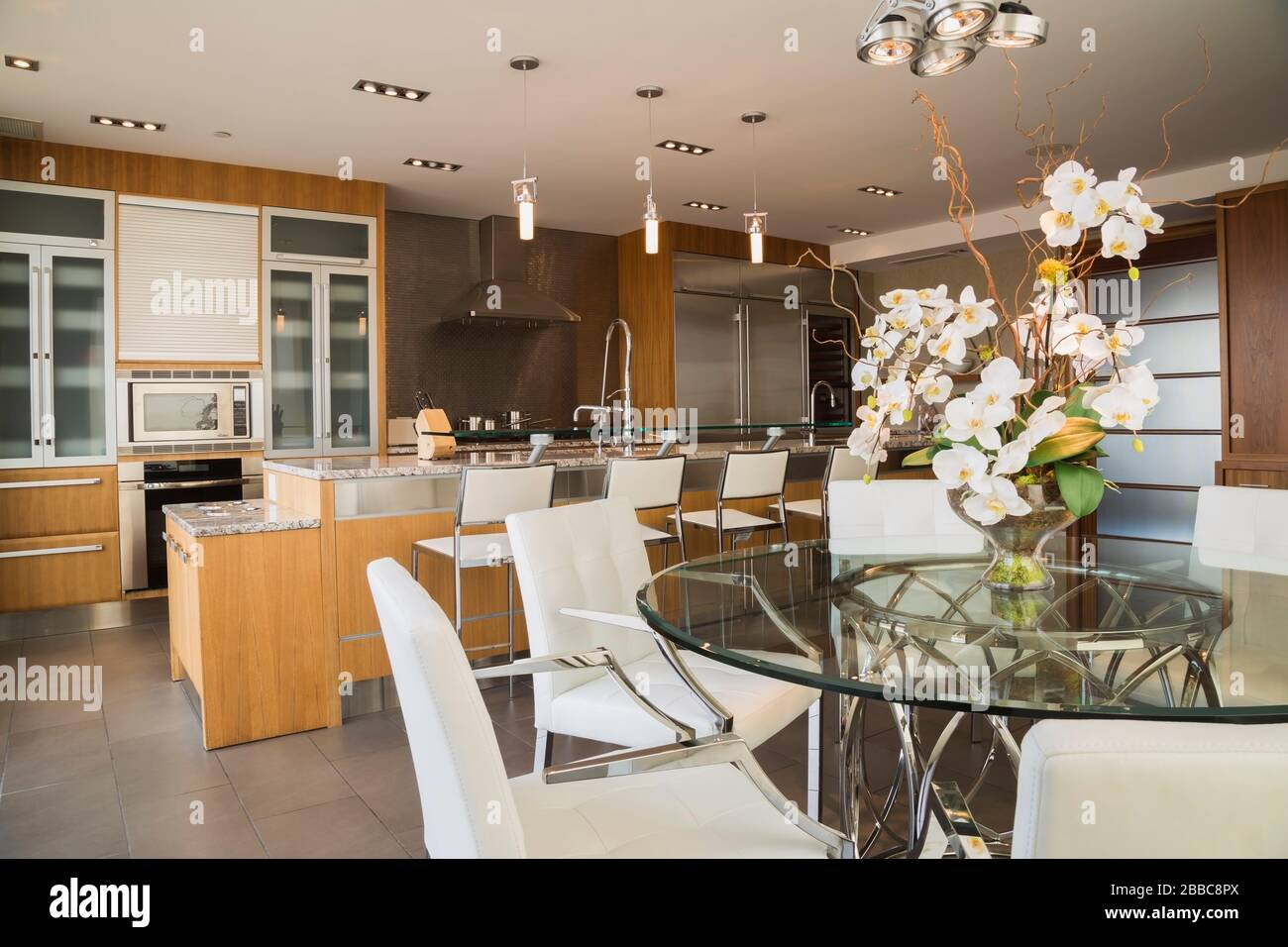 Picture of: Round Glass Dining Table With White Leather And Chrome Armchairs Wood And Glass Cabinets And Island